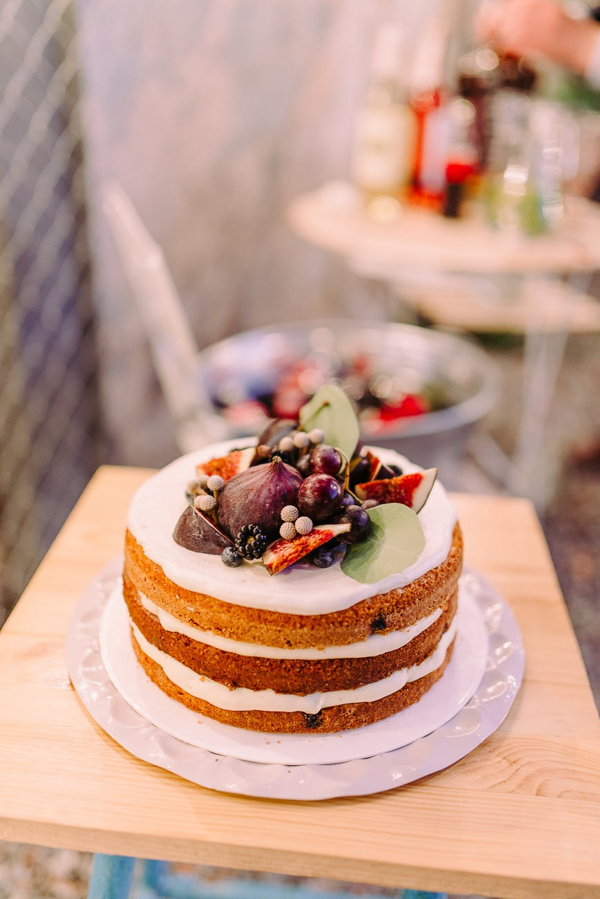 white icing covered cake in bokeh photography